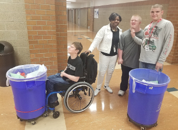 Sophomore Kaden Cook, para Frankie Williams, sophomore Jeff Evans   and senior Will Parish travel around the school,  taking out the recycling.