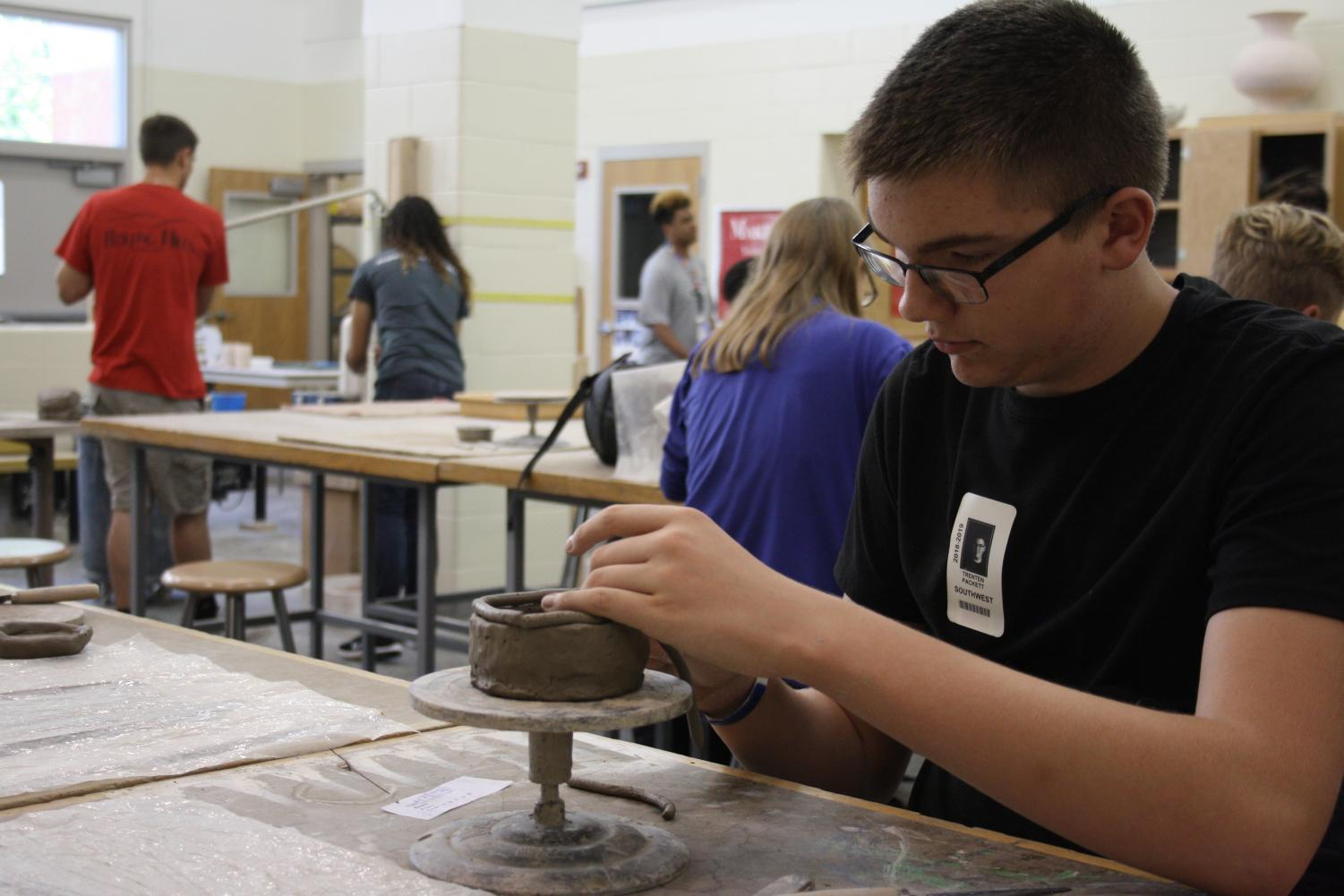 Freshman Trenten Packett smoothing out his coil pot in beginning pottery class.