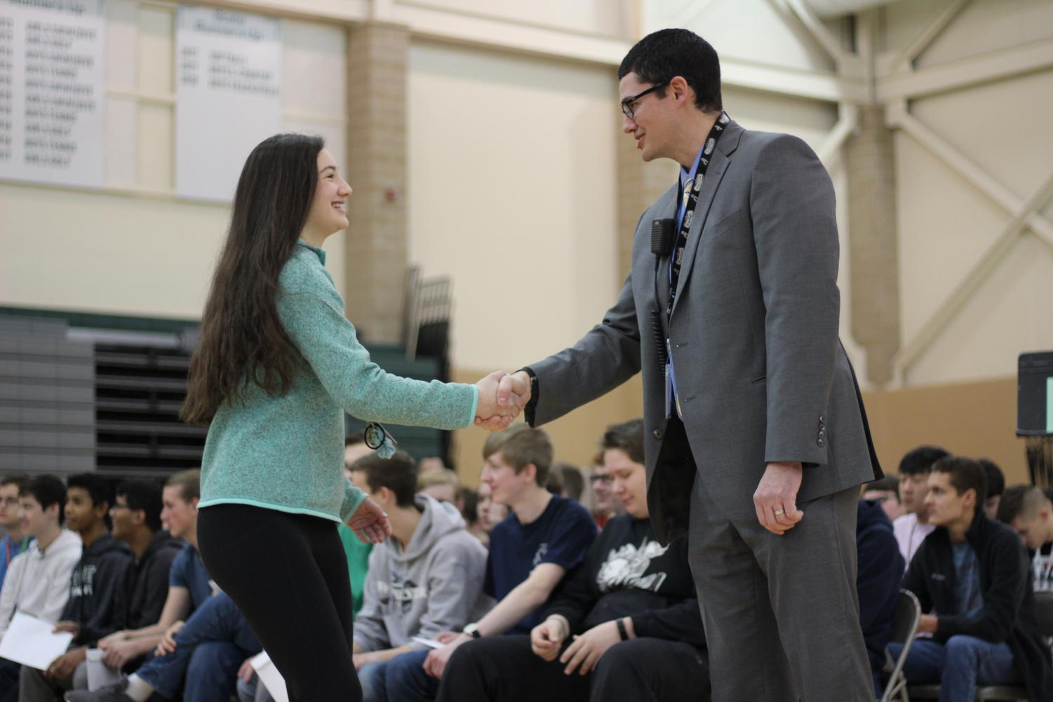 Sophomore Ava Spinar shakes Principal Michael Gillotti's hand during Honors Convocation on Thursday, Feb. 21.