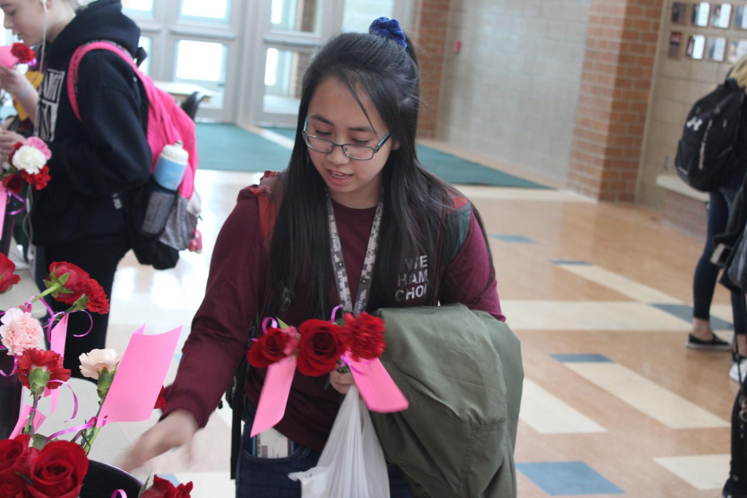 Senior Kim Cao picks up her flower order. Students can place orders for flowers until Wednesday the 13th from tables set up in the commons.