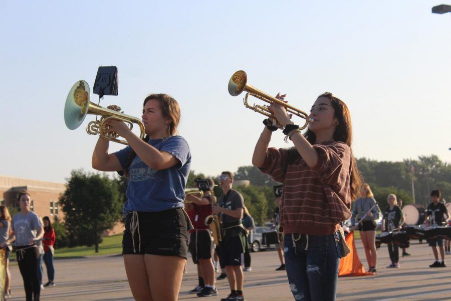 Junior Tenley Katt and sophomore Shayla Cordova set their drill during zero hour marching band practice. The show this year honors the 50th anniversary of the Apollo 11 mission.