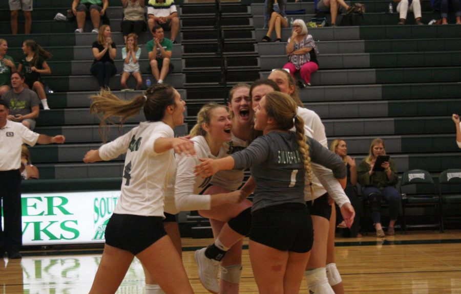 Members of the varsity volleyball team celebrate the 3-2 win over Kearney.