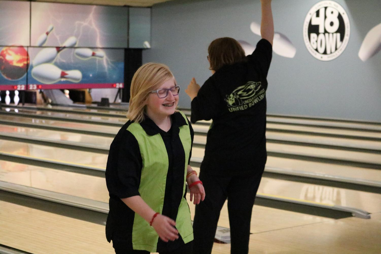 Freshman Josie Ulrich smiles after her turn to bowl. The Hawks lost 3,219 pins to 3,833.