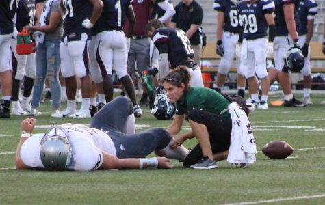 Athletic trainer Rebecca Townsend helps an injured player on the field during the Southwest vs. Southeast game.