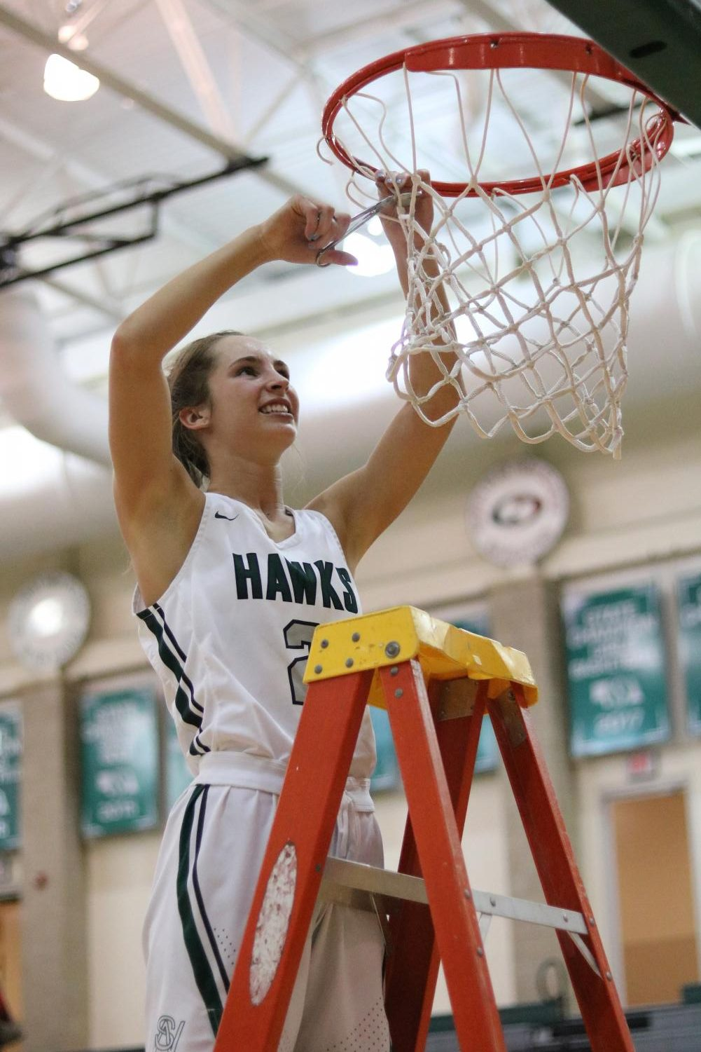 Senior guard Emma Kauf cuts down the net after Southwest's 45-20 victory over Southeast last Friday. The Hawks will play Omaha Westside on Friday at Pinnacle Bank Arena. Tip-off will be at 3:45 p.m.