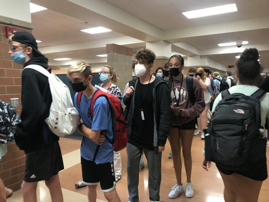 Students walk through halls while wearing masks.