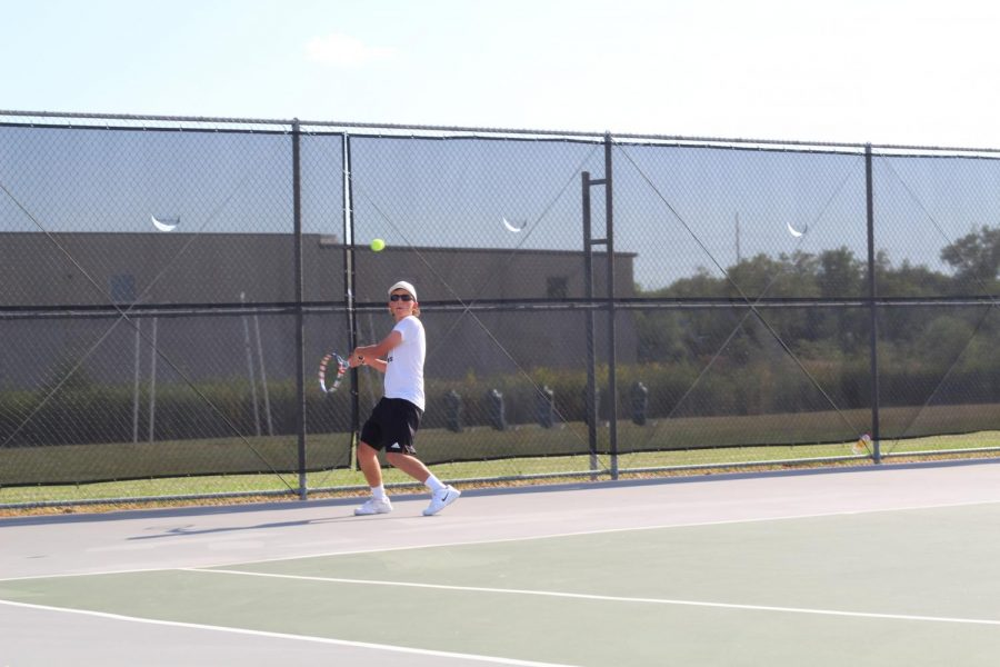 Logan Finley plays a singles match against a player from Southeast.